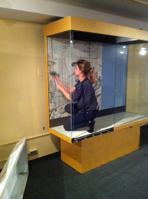 Graphics specialist Kate Fleming installs a graphic to the back wall of a case.
