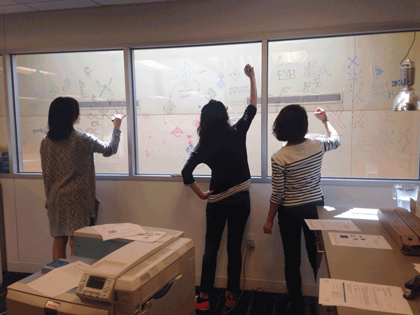 Designers Oona Ahn, Emily Sloat Shaw, and Kristen Orr work with potential logo designs.