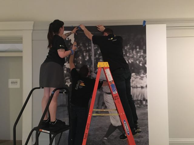Smithsonian Exhibits graphics specialists Sharon Head, Mike Reed, and Evan Keeling work as a team to ensure a smooth and seamless installation. (Again, in our line of work, that's literal.) Photograph: Caroline Chang