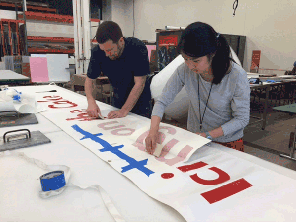 Graphic specialist Evan Keeling and intern Caroline Chang apply vinyl to a banner.