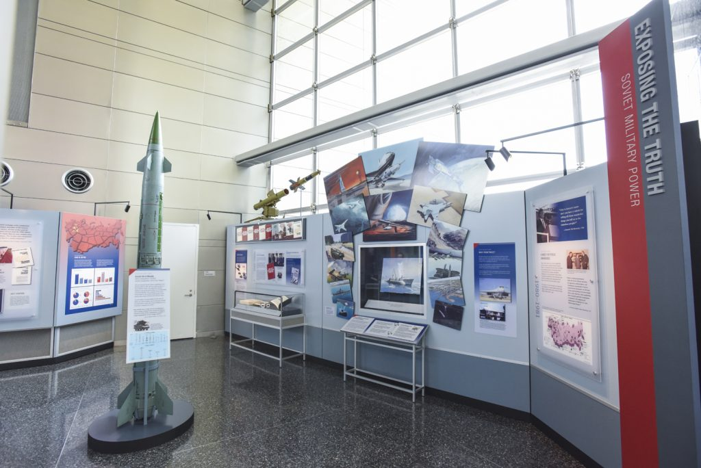 Museum display of artwork from the Soviet Military Power books and examples of Soviet missiles.