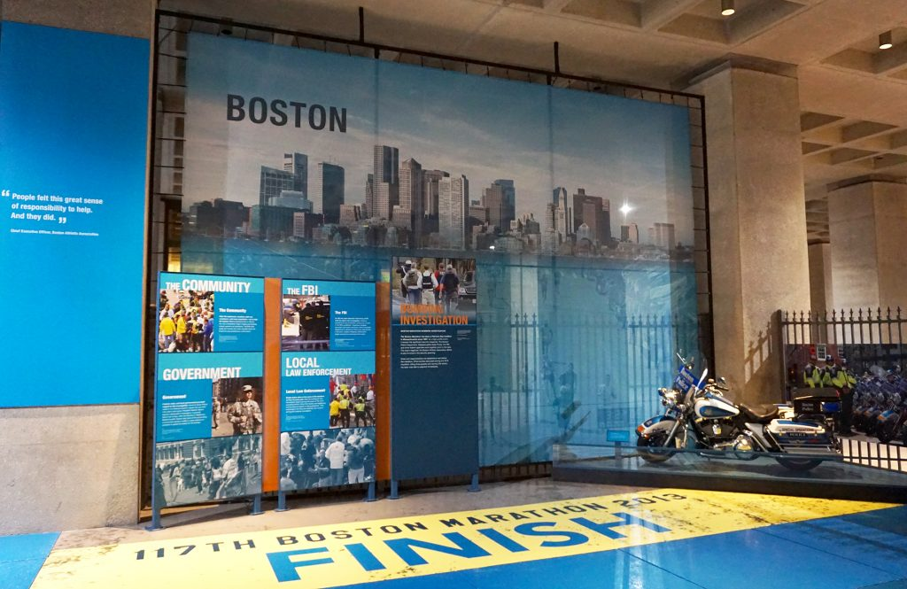 "Mural of the Boston skyline and marathoners, museum panels, and the quote from the Boston Marathon CEO ""People felt this great sense of responsibility to help. And they did."""