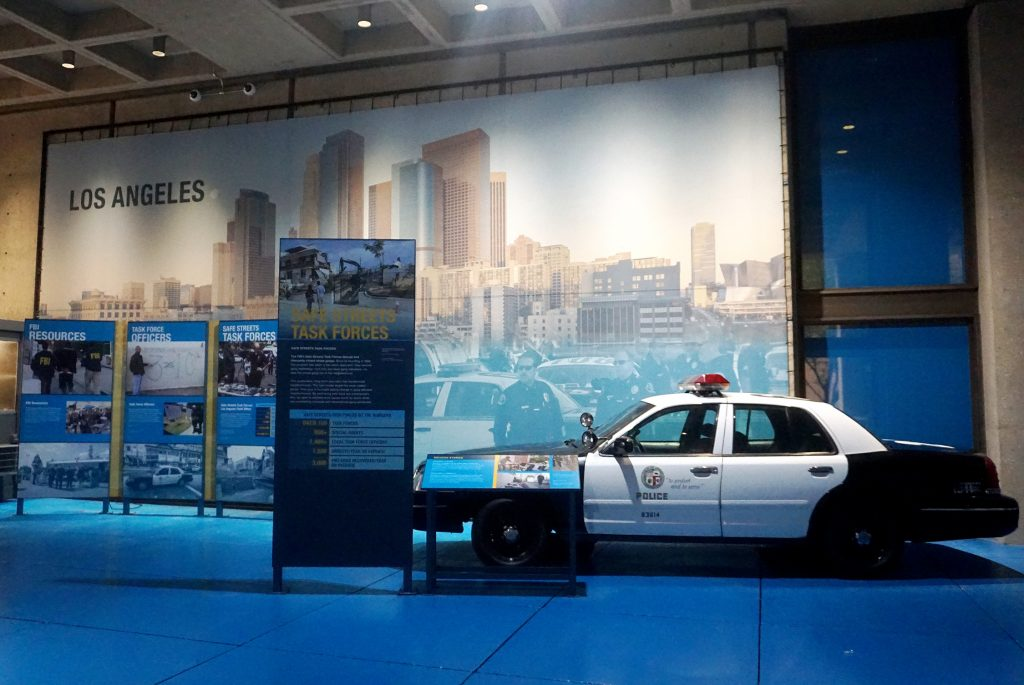 Mural of the Los Angeles skyline and police officers behind museum panels and an LAPD cruiser.