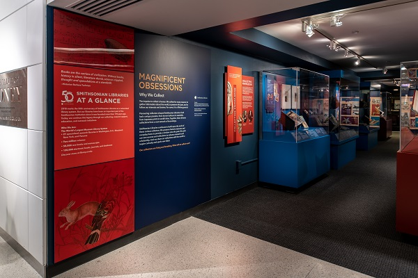 "Text on the wall on a red and blue background includes the words, ""Smithsonian Libraries at a Glance,"" and ""Magnificent Obsessions: Why We Collect."""