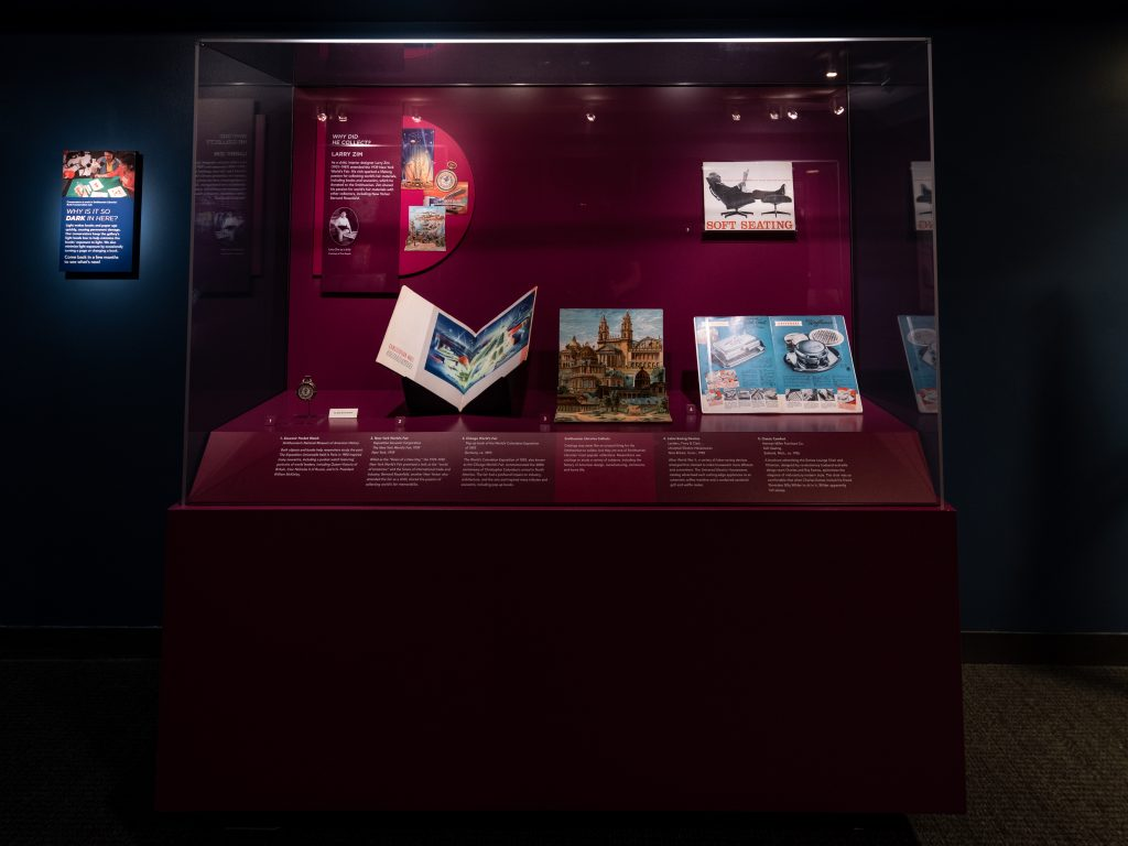 A purple display case contains four books and a pocket watch. The book at the center of the case depicts an elaborate building.