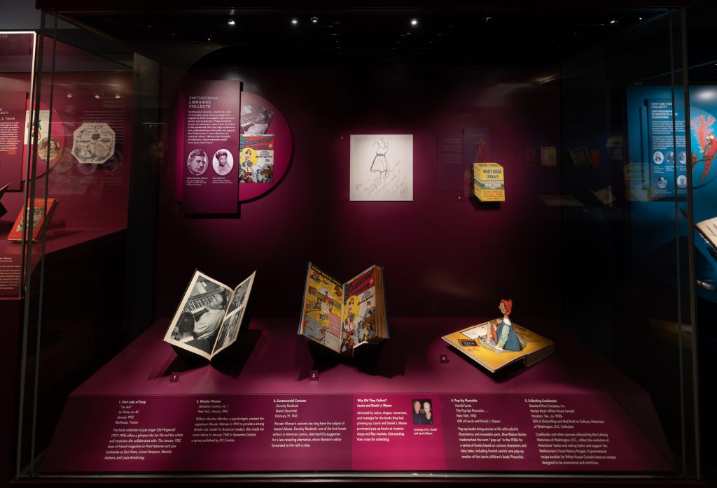 A purple display case contains four books and a print. The book at the lower right includes a pop-up illustration of the children's book character Pinocchio.