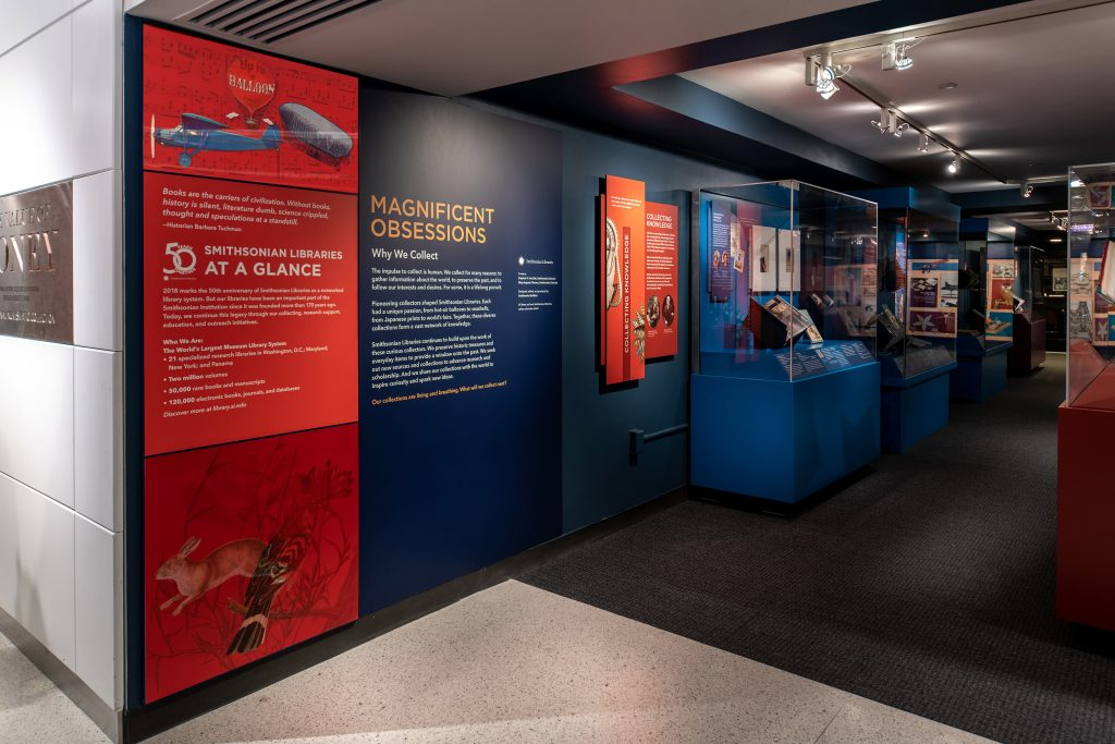 "Red and blue panels line the entrance to a gallery with the headline ""Magnificent Obsessions: Why We Collect."""