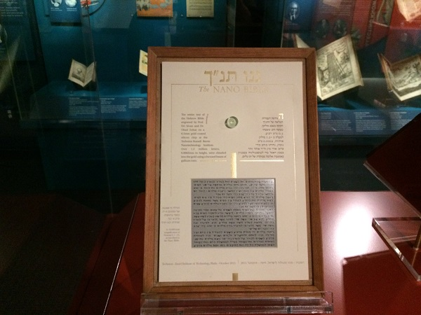 "A framed piece of paper includes Hebrew letters and the words ""Nano Bible"" in gold at the top of the page. Below these are a tiny magnifying glass."