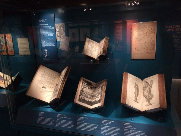 Four books and a letter are seen inside a display case with a dark blue background.