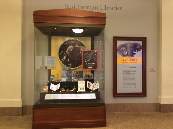 "A display case containing books, objects, and images of elephants stands next to a panel on the wall titled ""Game Change."""