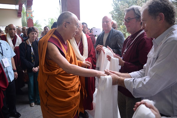 Scott grasps the hand of the Dalai Lama while holding a white scarf. A group of people stand and watch.