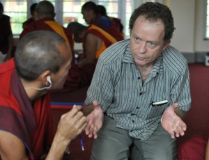 Scott speaks with a monk as they kneel on the floor