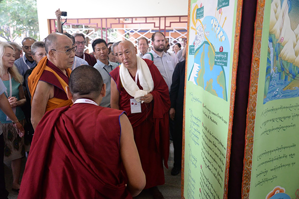 The Dalai Lama and two other monks look at an exhibit panel with a crowd of people in the background.