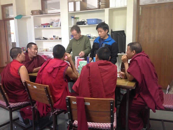 Scott stands with another man at a table where five monks are sitting.