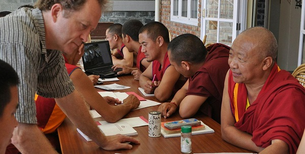 Scott leans forward and speaks to a monk sitting at a table. Other monks also sit at the table.