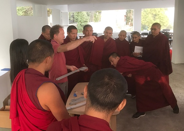 Scott holds a piece of equipment and gestures in front of a group of monks