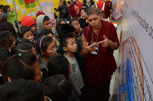 A monk stands in front of an exhibit panel and gestures to a group of male and female students.