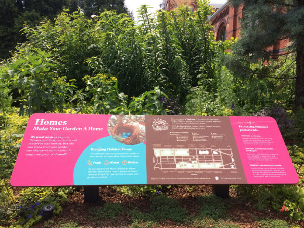 "A pink, blue, and brown exhibit panel in a garden, with the title ""Homes: Make Your Garden a Home"""