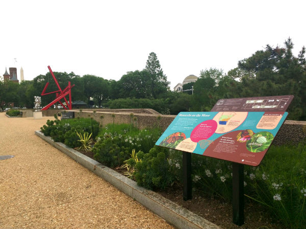 A pink, blue, and brown exhibit panel in a garden with an abstract red sculpture in the background