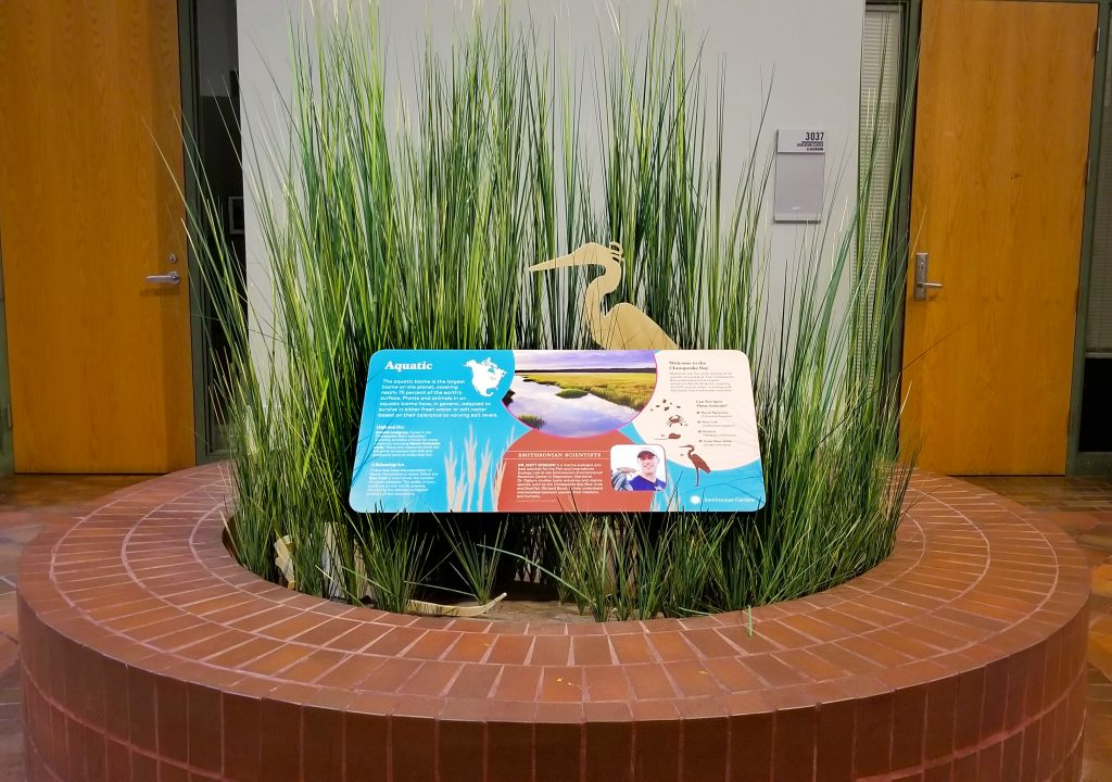A brick circle containing replicas of tall marsh grasses, an exhibit panel, and a cutout in the shape of a heron