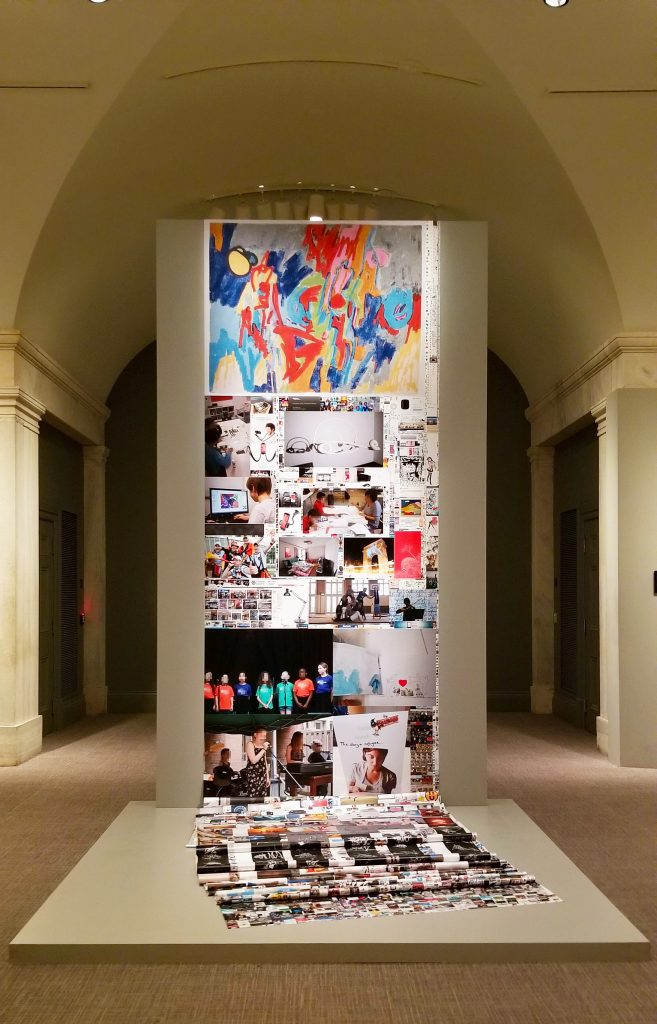 A tall L-shaped platform at the center of a gallery displaying multiple photographs