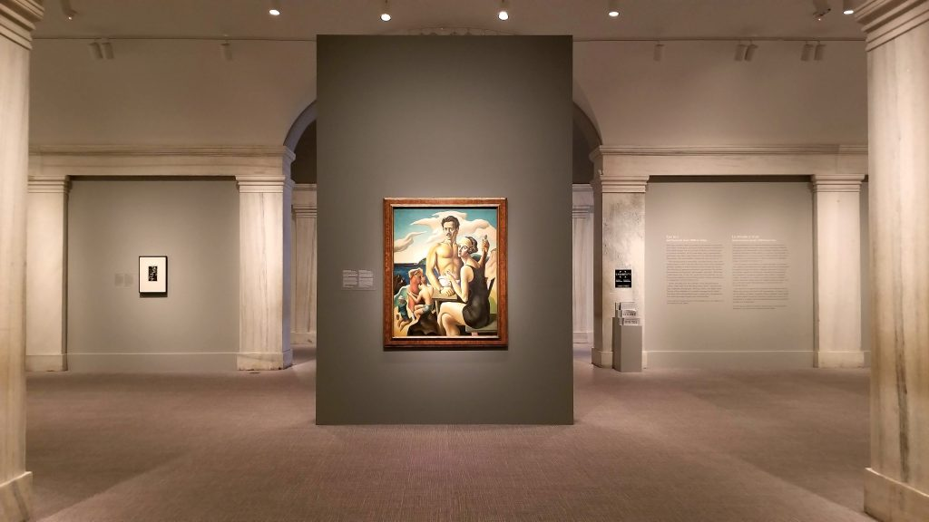 An exhibit wall at the center of a gallery featuring a painting of a man and a woman
