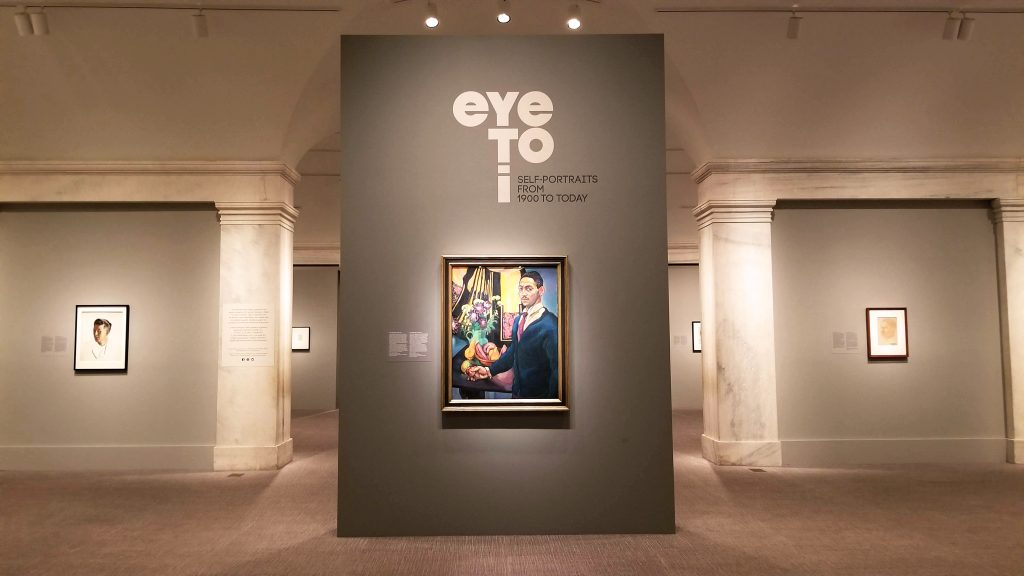 "An exhibit wall at the center of a gallery featuring a painting of a man and the title ""eye to i"""