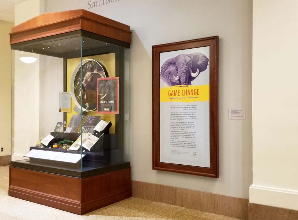 A text panel with an illustration of an elephant on it next to a display case containing books and other objects