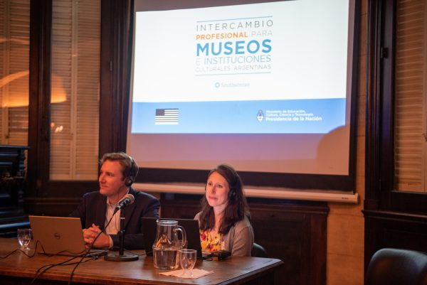 a man and a woman sit at a desk in front of a screen with the Spanish title Intercambio Profesional Para Museo e Instituciones Culturales Argentina