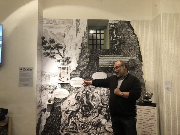 A bearded man points at a label in an exhibit