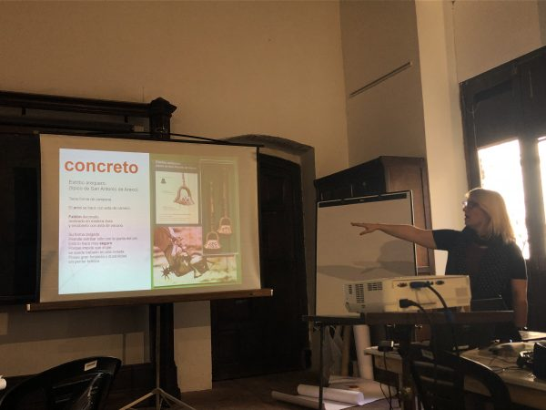 """a woman points to a screen with the Spanish word """"concreto"""" and tips for writing Spanish museum texts"""