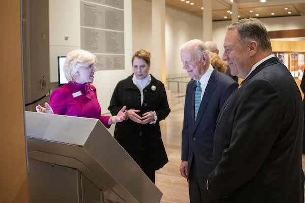 A woman in a magenta outfit gestures toward a touch-screen kiosk. Another woman and two men wearing suits look on.