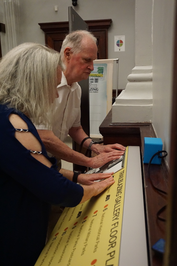 A man and a woman stand side by side in front of an interpretive panel on a reader rail and use both hands to touch it.
