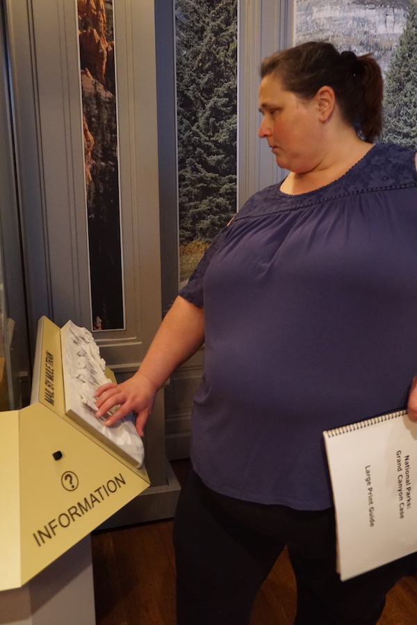 A woman touches a 3D model of a mule mail train on a reader rail.