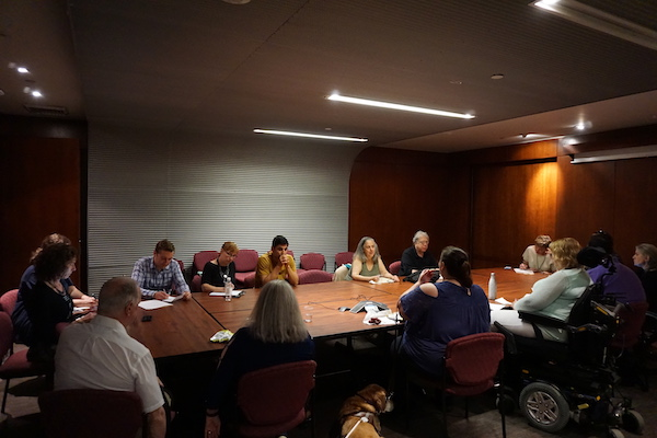 A group of 15 people sit around a table in a conference room. Several service dogs lie on the floor.