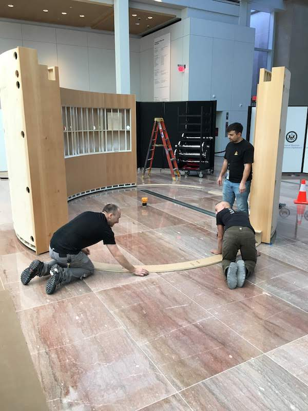 Three men install a large wooden exhibit module on a pink marble floor