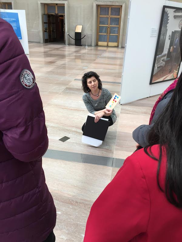 A woman crouches on the floor holding a card showing color samples