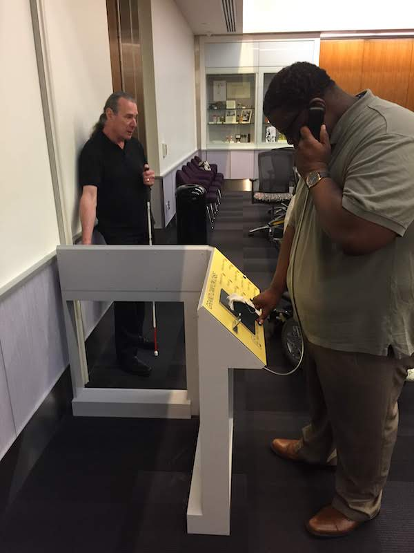 Two men stand next to an L-shaped reader rail. The man on the left touches the reader rail with his right hand and holds a white cane in his left hand. The man on the right touches the reader rail with his right hand and holds an audio handset to his ear with his left hand.
