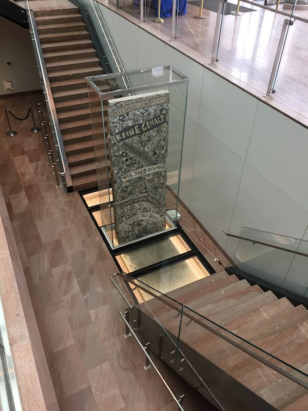A segment of the Berlin Wall in a glass case at the bottom of two sets of stairs