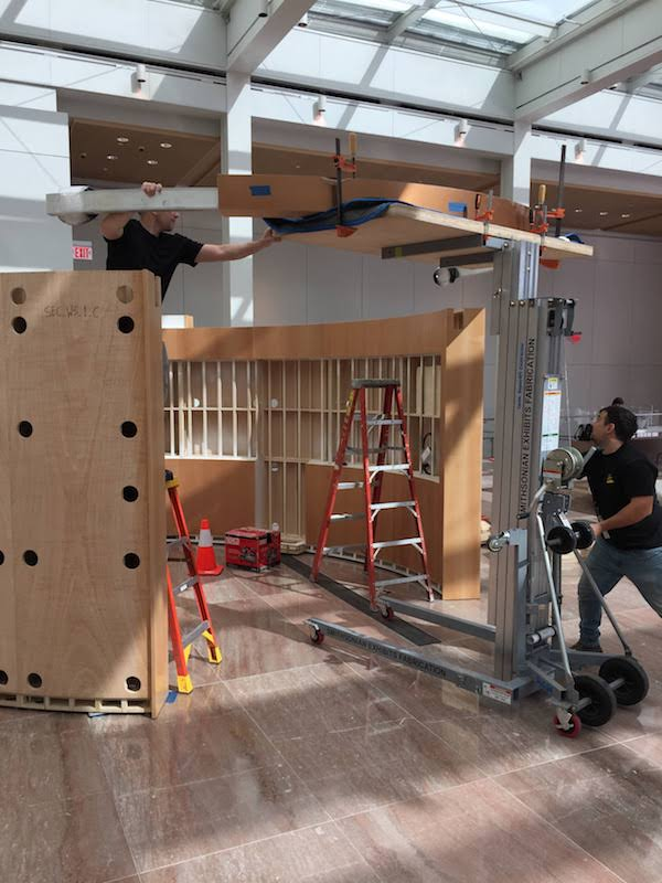 A man operates a forklift to lift a curved wooden and metal structure up to the top of a wooden exhibit module where another man standing on a ladder holds it.