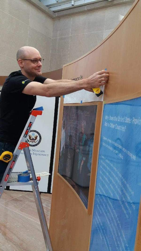 A man on a ladder attaches colorful graphics to a wooden exhibit module.