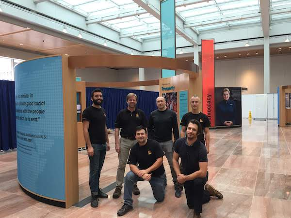 A group of six men pose in front of the exhibit.