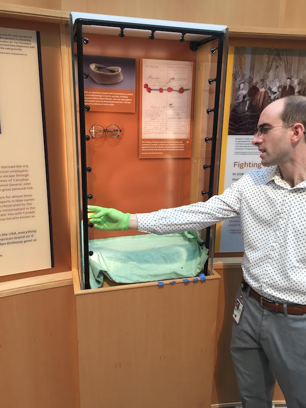 A man wearing green gloves opens a display case containing a pair of glasses.