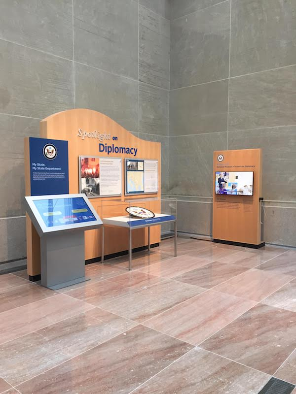 "Two wooden structures in a corner with a display case, a touch-screen kiosk, and a video monitor. The main panel is titled ""Spotlight on Diplomacy."""