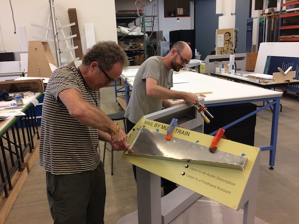 Two men use tools to attach elements to a reader rail structure.