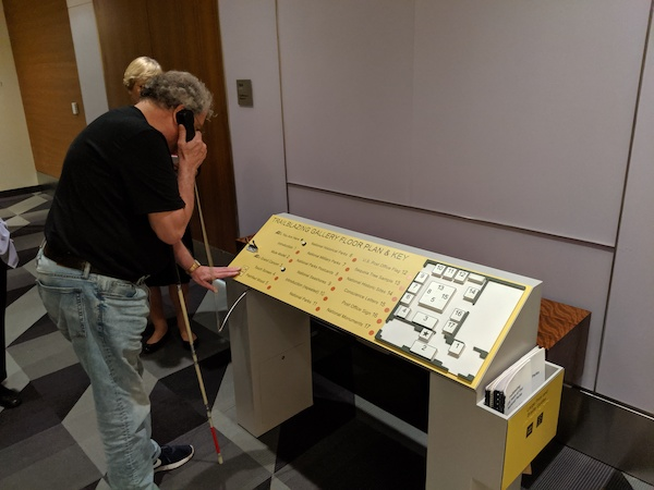 A man touches an interpretive panel on a reader rail with his left hand and holds an audio handset to his ear with his right hand.