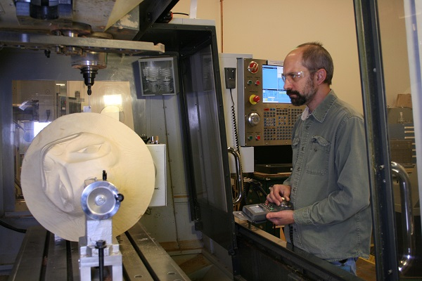 A man wearing safety glasses controls a computer-operated milling machine carving a wooden hat.