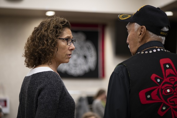 A woman wearing glasses speaks to a man wearing a baseball cap and a vest with a red design on it.