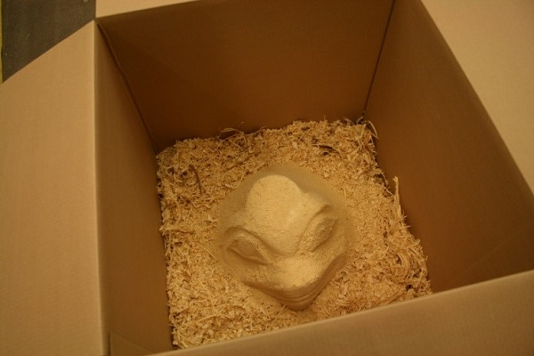 A carved wooden hat sits in a box full of wood chips.