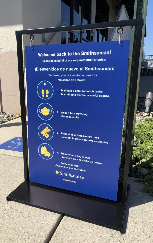 A blue graphic with white lettering and yellow icons welcomes visitors to the National Zoo. It lists the requirements for staying six feet apart, wearing a face covering, presenting a timed entry pass, and to prepare for a bag check. The graphic is in a black metal frame; the graphic can swing in the breeze to prevent the wind from knocking it over